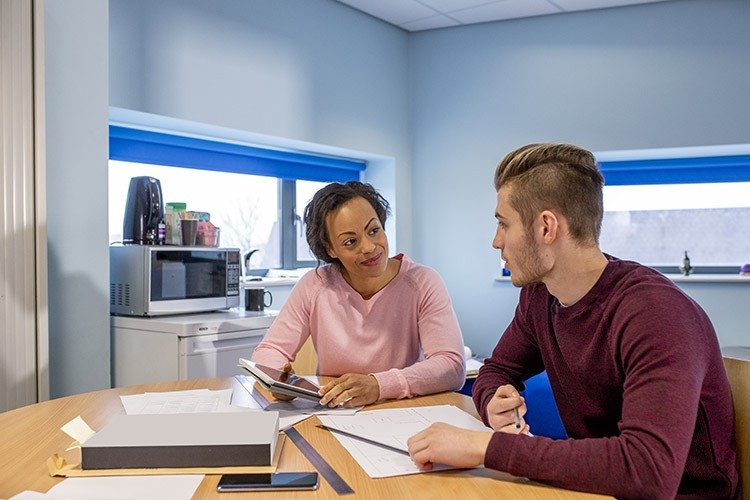 Spotlight On: Employability Practitioner Level 4 Apprenticeship - Two individuals looking at each other whilst sat at a desk