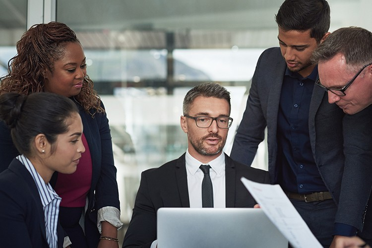 The Apprenticeship Levy: Top Tips to Maximise Your Funds in 2020 - A group of professional individuals working around a computer